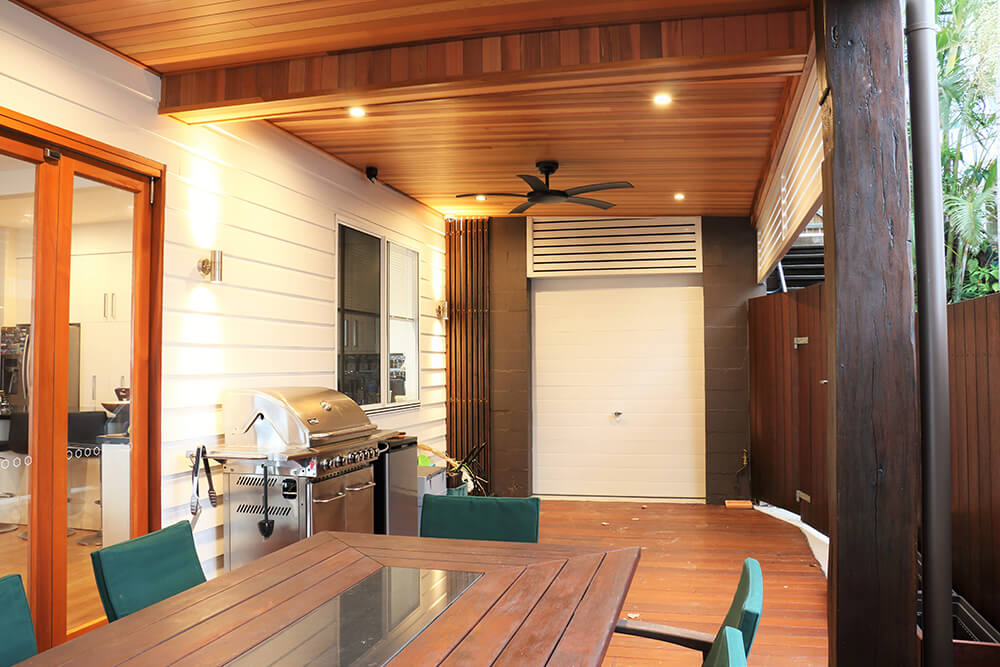 The home's deck features an outdoor kitchen and a dining table set for eight.