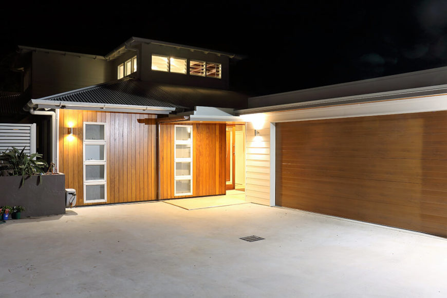 Moving around to the front of the home, we see how the cedar panels help unify the entire structure, appearing on feature walls both indoors and outdoors, as well as the large garage door to the right.