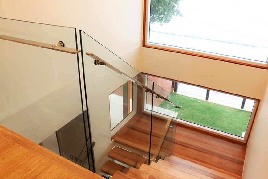 The completely remodeled stairway features an open design, glass balustrades, and large windows that allow light and air to pass through all three levels of the home.