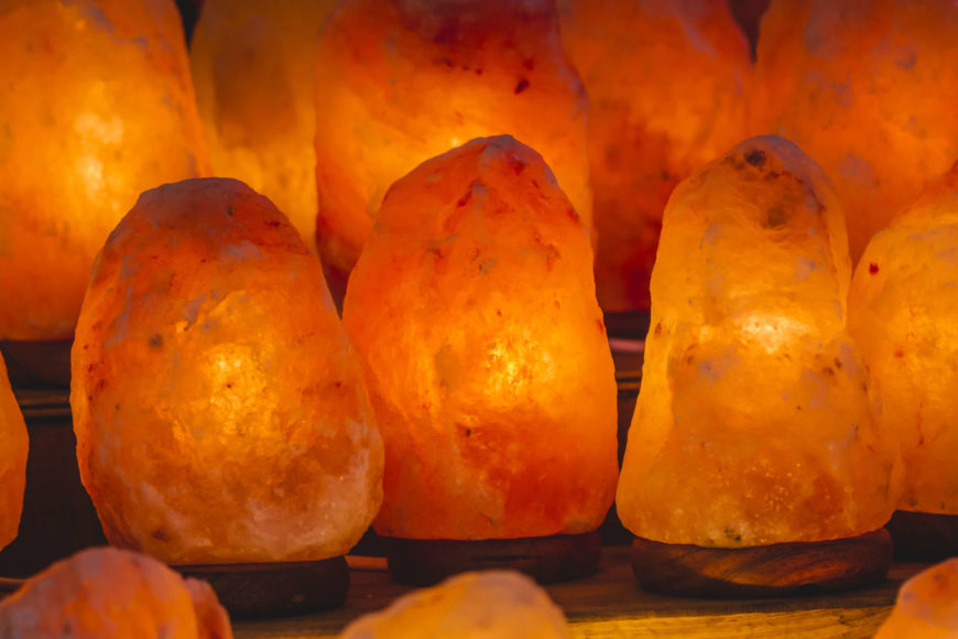 Himalayan pink salt lamps are said to purify the air through hygroscopy. They attract water molecules from the surrounding environment, absorb those molecules and any allergens they may be carrying. As the water evaporates, it leaves the dust, allergens, or other particles trapped in the salt.