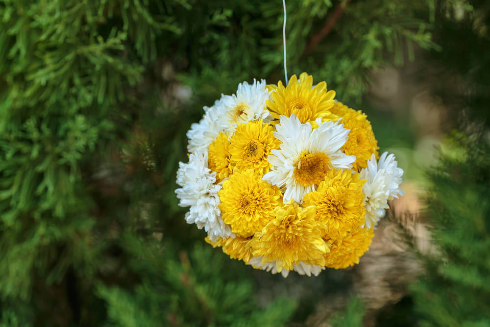 Example of hanging flowers without a basket. This is a woven quay of white and yellow flowers.