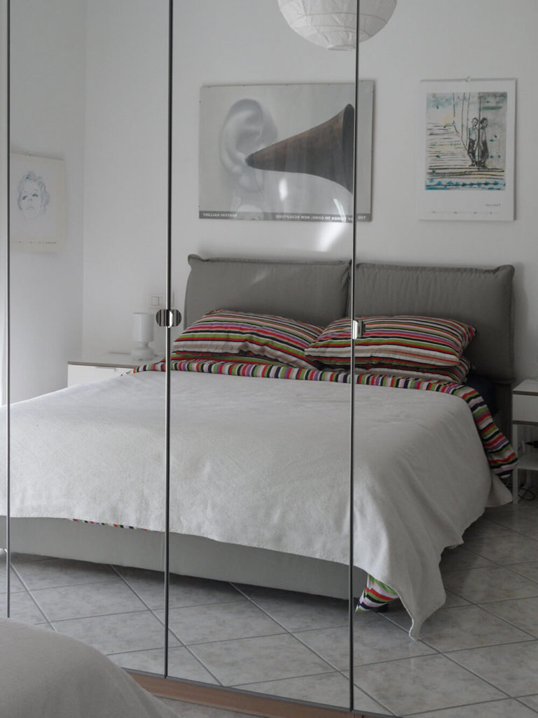 The bedroom is also a straightforward and elegant space with both minimal features and contemporary features. The tall mirrors seem to enhance the space, making it feel expansive. This, in conjunction with the well-orchestrated flow through the room, gives this small space an airy feel.