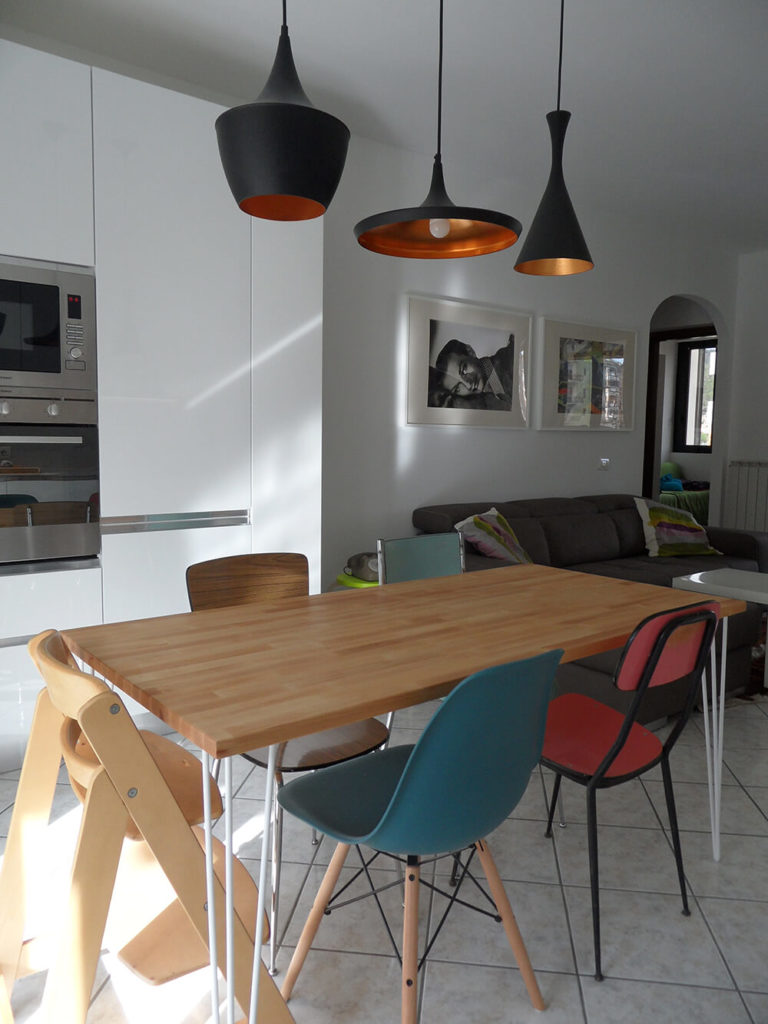 The dining area is right off of the living room space. The seats here all differ in style, shape, and color. The drama of the space is built up through this contrast.