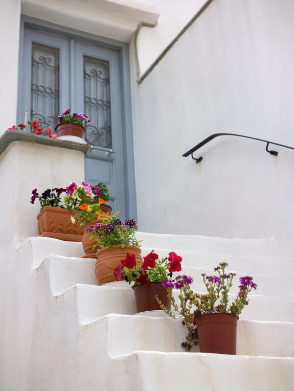 White is an emblem of purity and any colorful flowers placed along it will standout. These outdoor steps feature a white colored background decorated with small brown painted pails and clay pots that serve as guardrails.