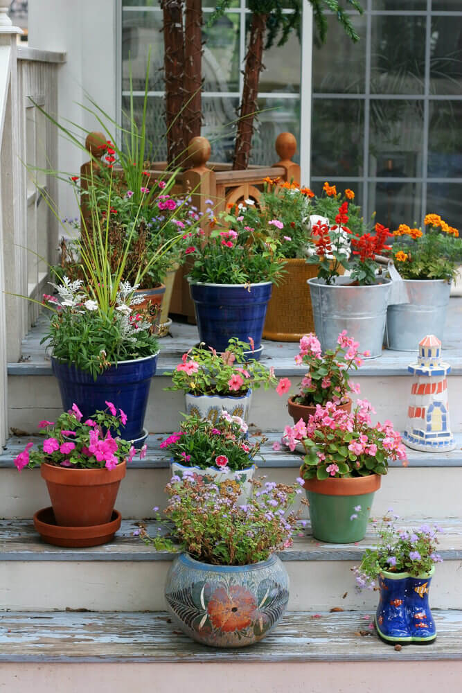 A mixture of boot shaped and round ceramic pots, blue and painted clay pots, and metal pails are wonderful together, especially with blossoming flowers like begonias and petunias.