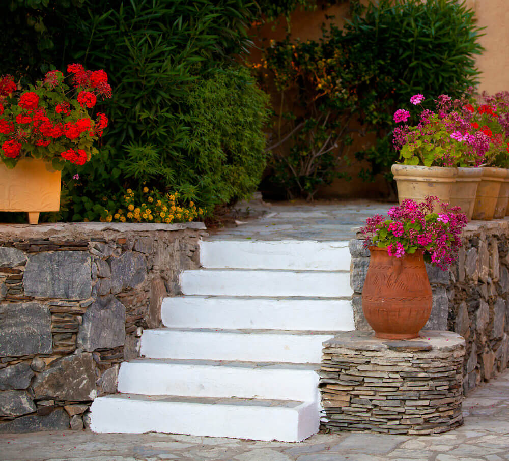 Rubble stone walls, white painted steps and clay pots with geranium blossoms are a great match. A single flower clay pot rests next to the steps while the other pots align on the upper floor.