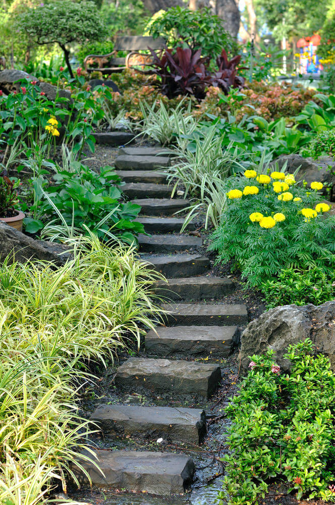 Black slabs of rectangular stones make up the steps between this garden of Japanese ornamental grasses, shrubs, and flowered plants.