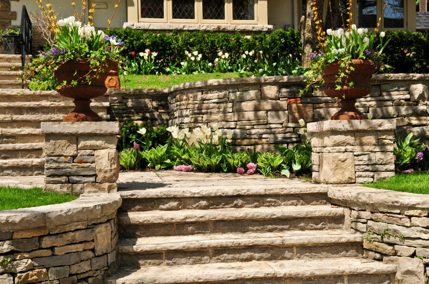 This outdoor garden surrounded by slabs of concrete and stone gets its warmth from the green of the landscaped Bermuda and the full bloomed colored flowers on the sides. Perched on two large clay vases are the colored flowers of white, purple, yellow, and some vining shrubs.