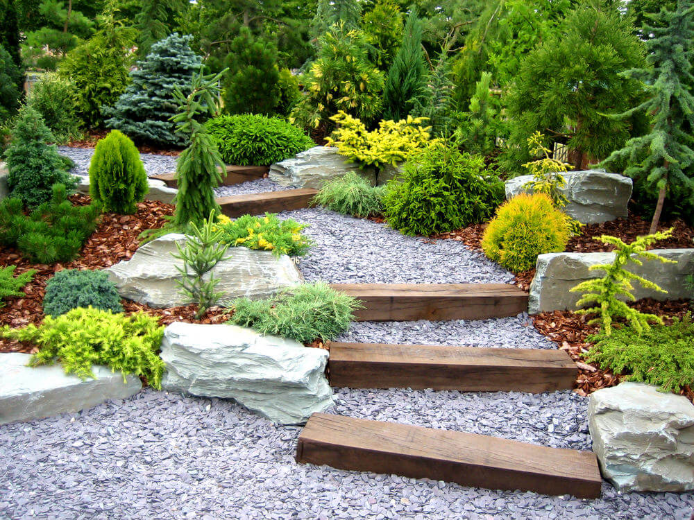 A well-trimmed variety of evergreen shrubs makes way for the garden steps of pebbled stones and occasional wooden slabs. Some bleach colored boulders are also used in between the shrubs to allow for enough space.