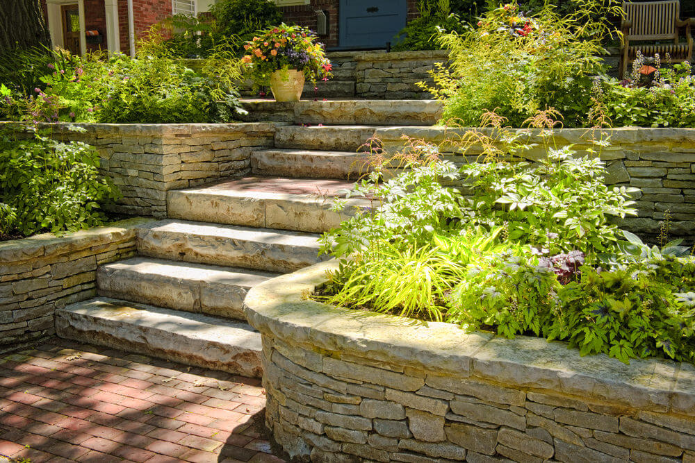 Sunshine greets the garden shrubs that are harmoniously tucked in these landscaped stone-styled planters juxtaposed with concrete garden steps and brick floor.