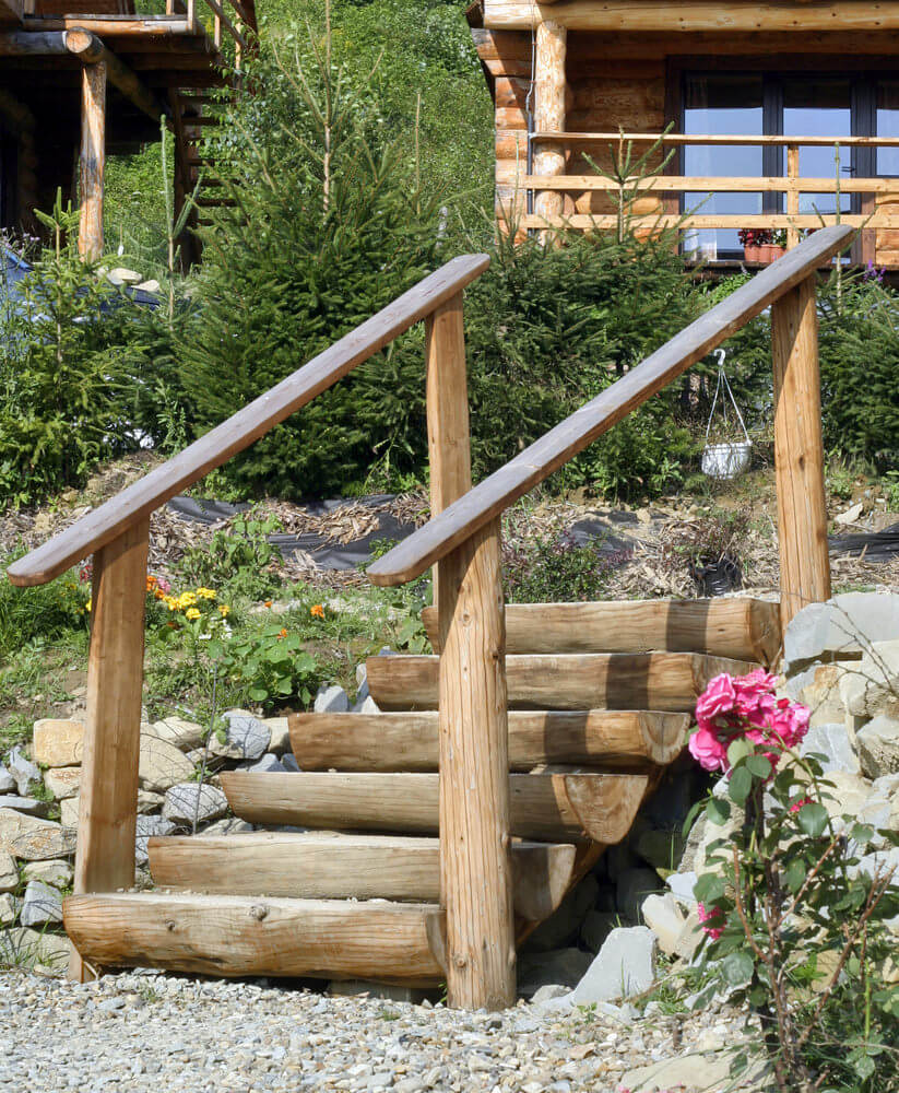 The log house overlooks a garden of small pines and shrubs before a wooden staircase that leads to a sea of bleached pebbles and large stones, where flowering plants like pink roses are seen standing nearby as if on guard.
