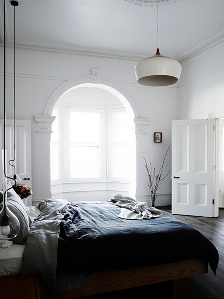 The master bedroom continues the mixture of dark hardwood flooring and white walls, with a more ornate, old-fashioned look. Bedside light is provided by a pair of uniquely long pendant lights, wrapped in glass.