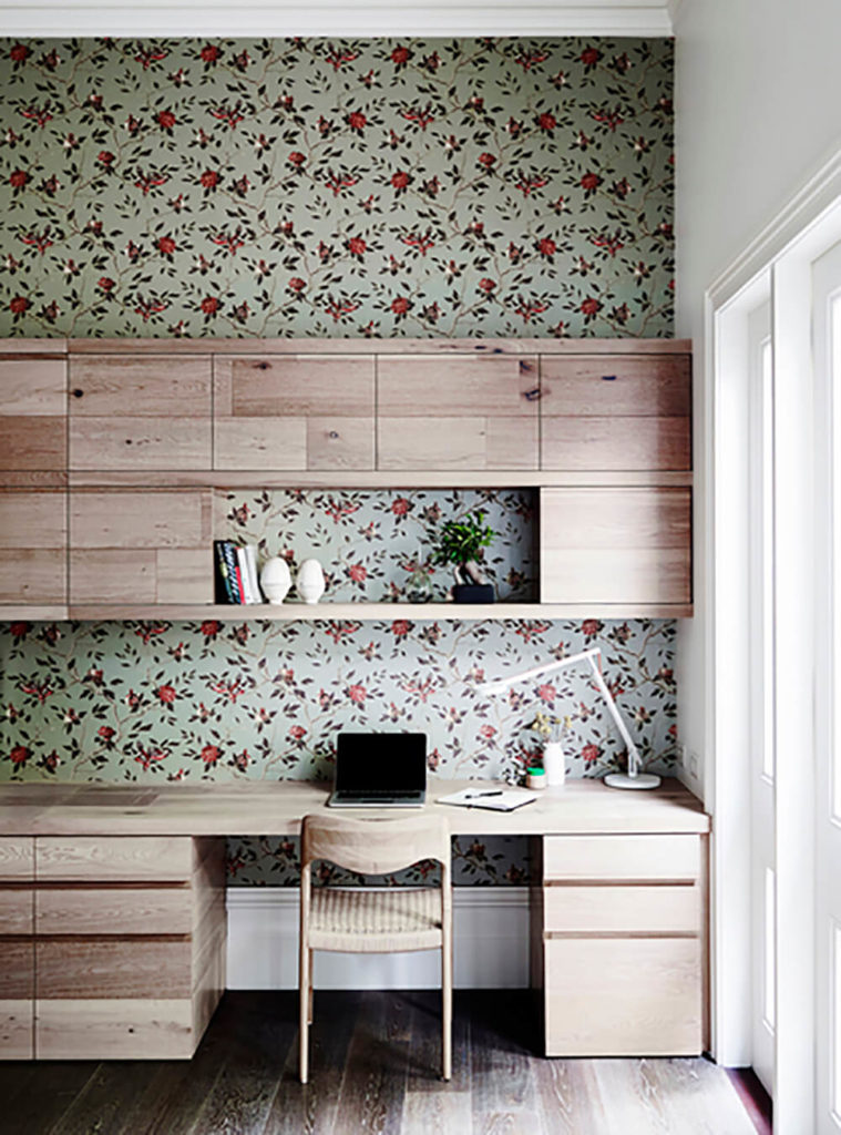 This home office provides a rare burst of color in the home, with floral wallpaper backing the rich natural wood desk.
