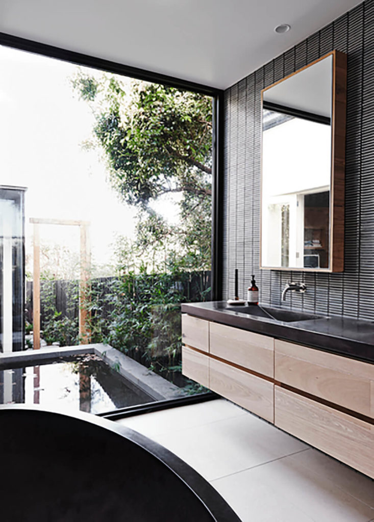 The master bath features a massive window for expansive views over the landscape. With a floating vanity and large, oval shaped soaking tub, it's a comfortable and handsome space.