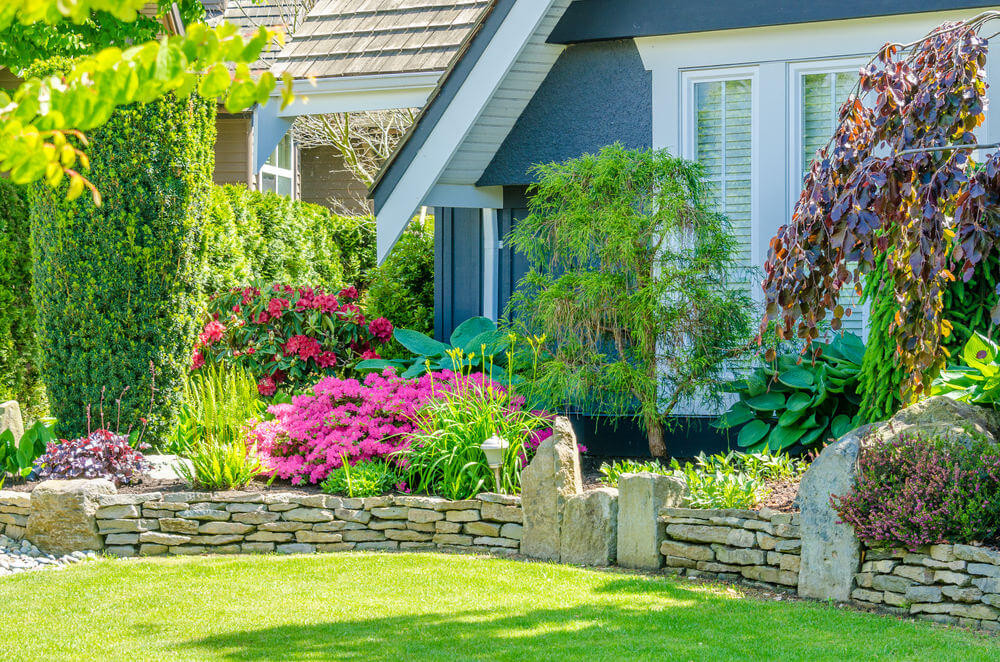 Brick stone edging looks more fabulous when ornamented with landscaping grasses and colorful blossoms.