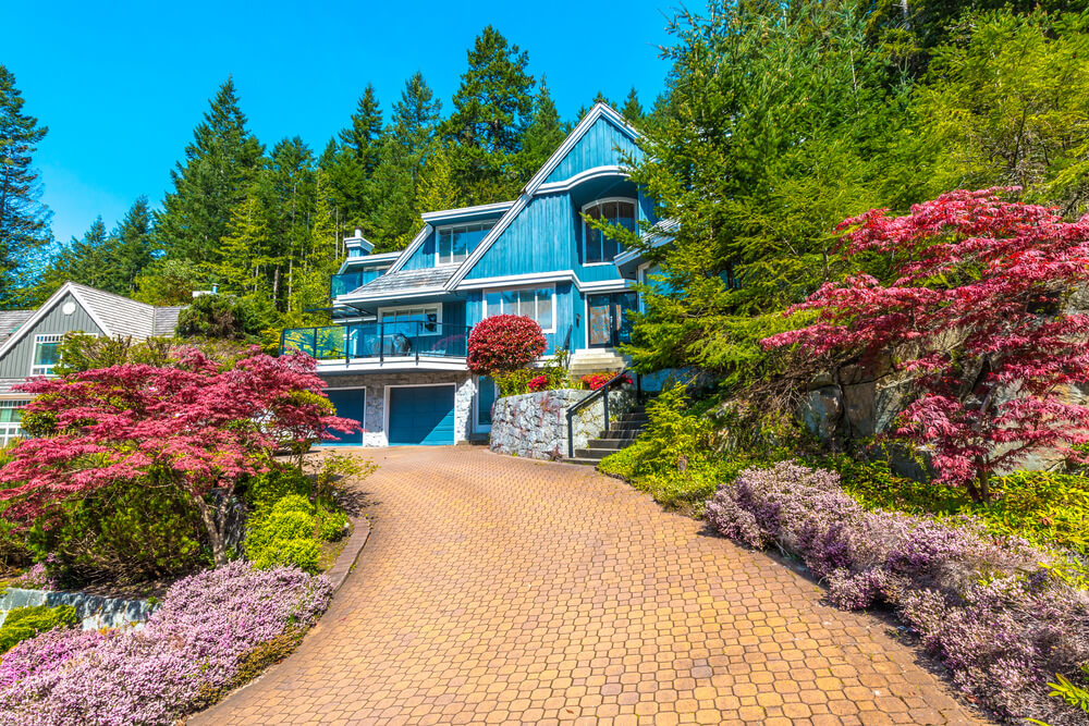 The blue house attracts most, thus the colors from its surrounding must also blend to balance a good view. The color of the brick pathway, Japanese Palmatum maple trees, green pines and shrubs are a good combination.