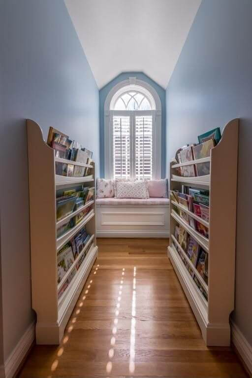 This space may not have initially been used for much but was cleverly turned into a seating area with plenty of shelf space for displaying books. This cozy reading nook is a creative use of the space.
