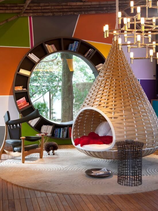 Here is an example of how you can be creative and make your reading space unique. The striking chair, hanging basket seating, and massive round bookcase framing the window are all elements that make this space stand out and draw you in before you even crack open a book.