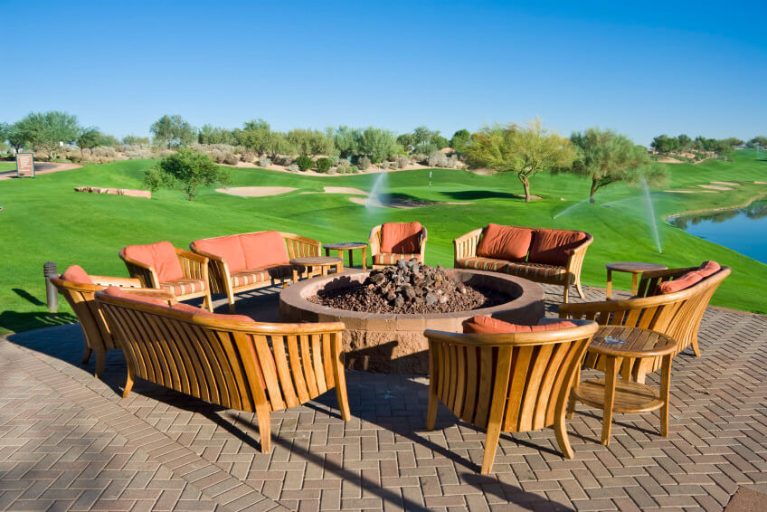 Large round brown brick fire pit on a matching brick patio over looking a golf course.