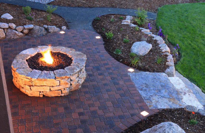 Round rock fire pit on brick patio overlooking Gardens and Yard.