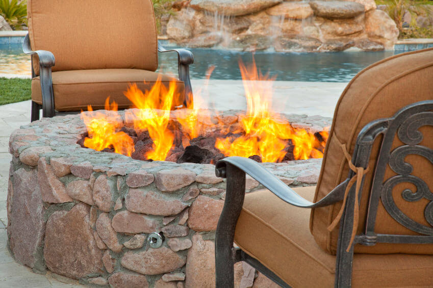 Close-up of a round stone fire pit built onto a brick patio overlooking the pool.