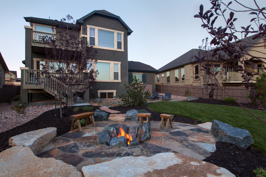 Patio fire pit dug into the ground surrounded by large rocks. - 42 Backyard And Patio Fire Pit Ideas