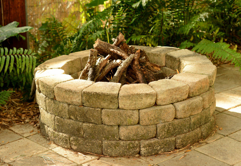 Massive round brick wood-burning fire pit placed on large patio.