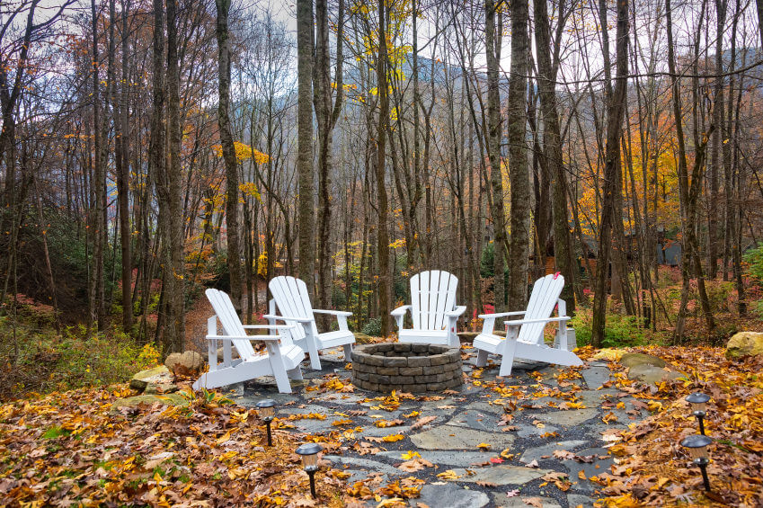 Flagstone Forest patio with brick round fire pit surrounded by striking  white Adirondack chairs. - 42 Backyard And Patio Fire Pit Ideas