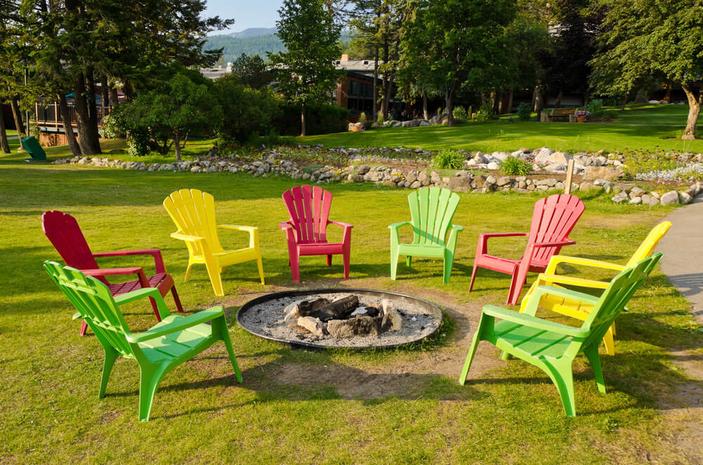 Dug in round fire pit with sand on grassy area surrounded by colourful Adirondack chairs.