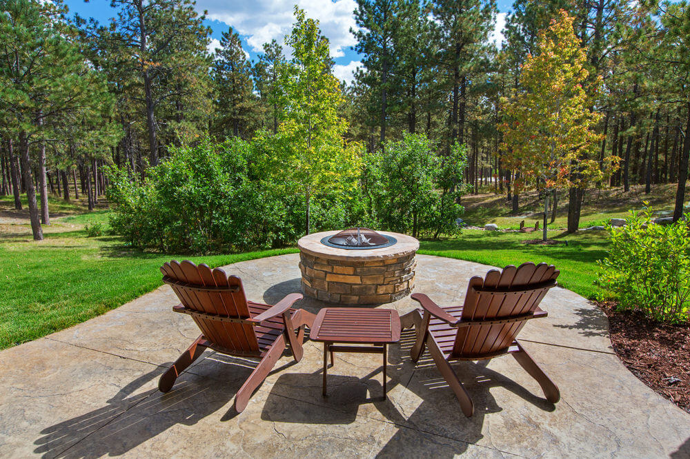 Beautiful Patio Overlooking The Forest And Sprawling Lawn With A Brick  Round Fire Pit That Has