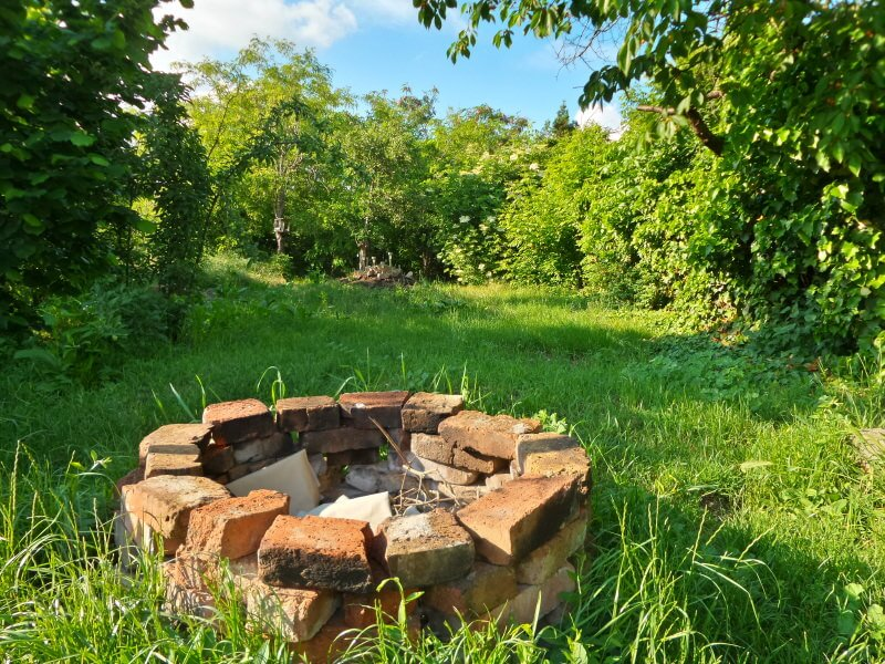 Rustic brick round wood-burning fire pit placed in the middle of the meadow.