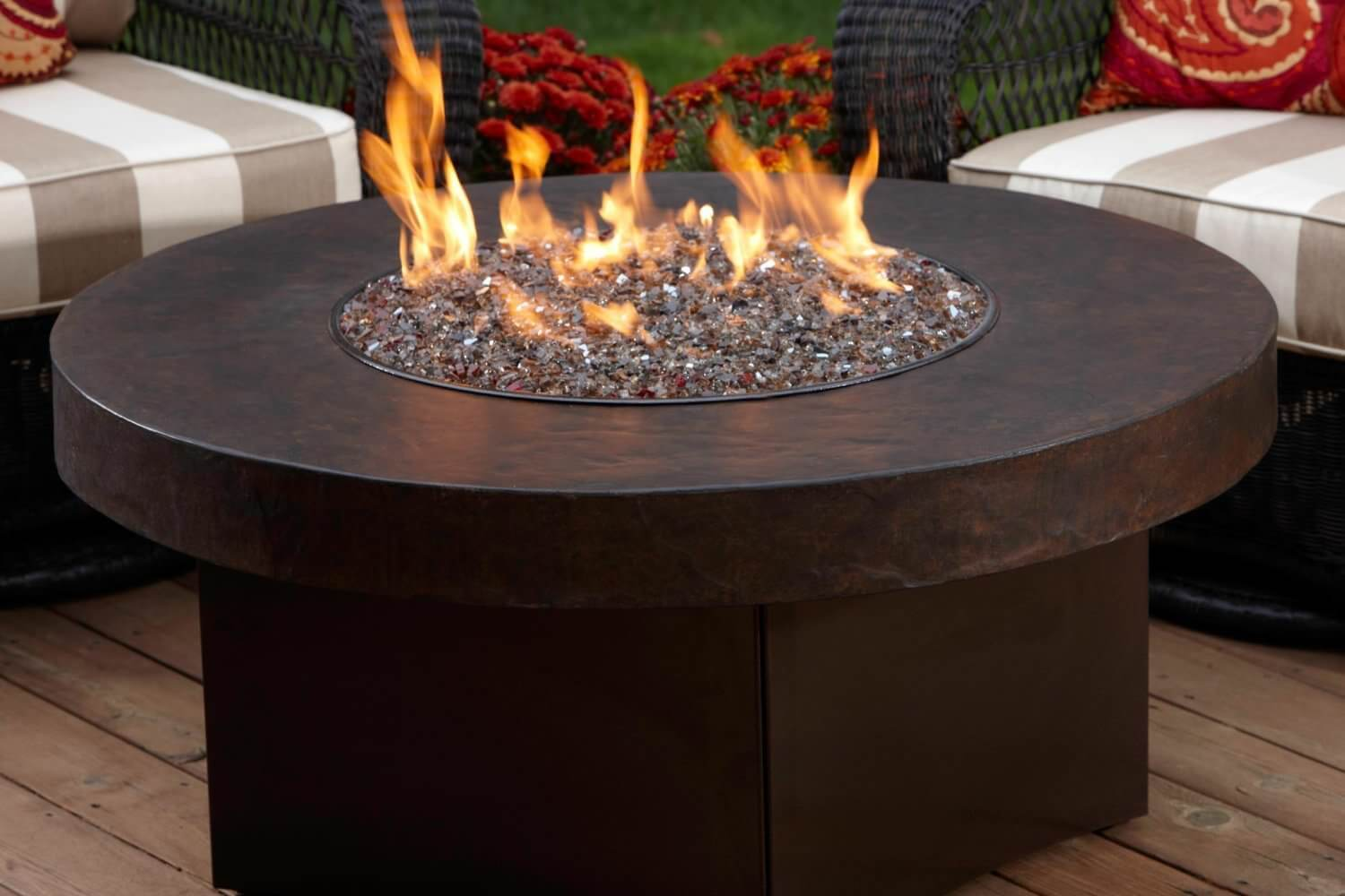 Large round brown metal gas powered movable fire pit with a square base and round top perfect for a patio or backyard area.
