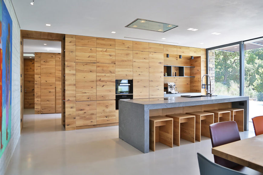 Turning the opposite way, we see the kitchen, absolutely flush with rustic style wood paneling from top to bottom. The large island features a built-in sink and plenty of room for casual dining.