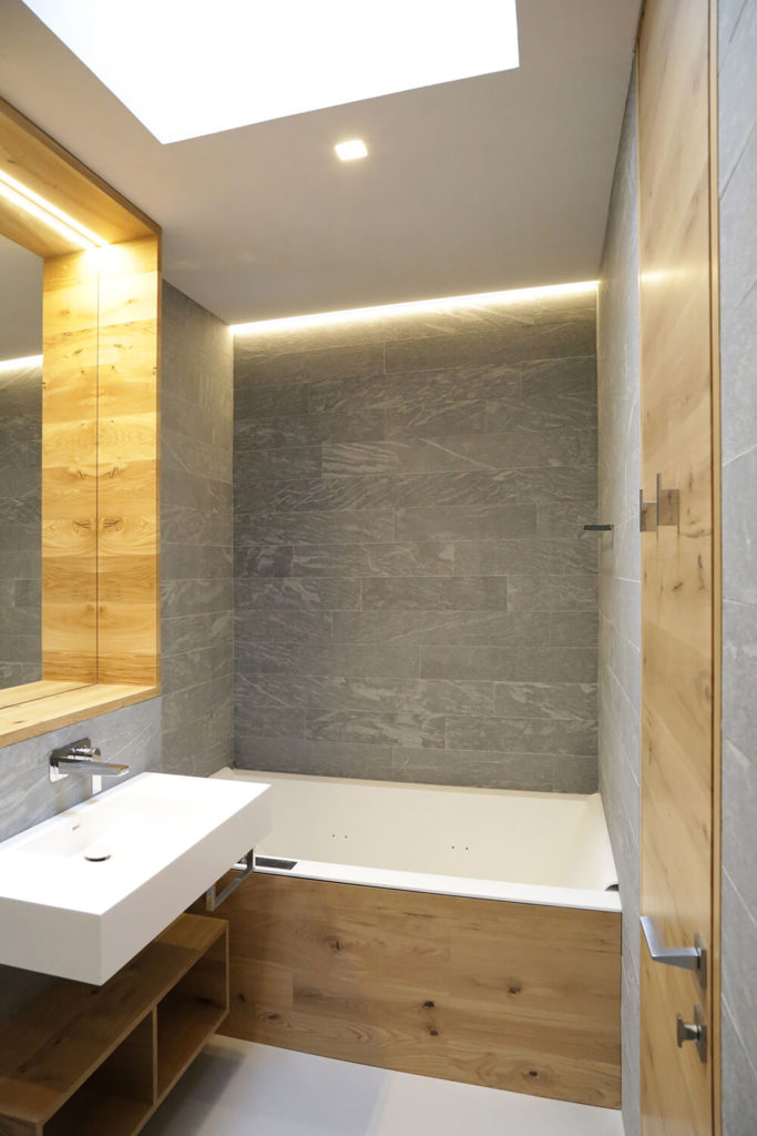 The bathrooms are flush with rich wood, from paneling around the tub and mirror, to creating a small floating shelf below the white vanity.
