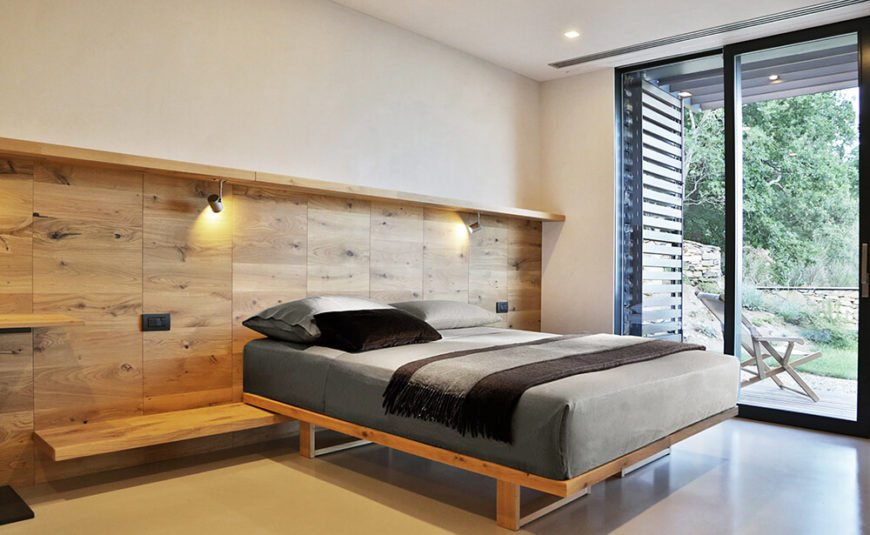 The master bedroom also holds floor to ceiling glass for a fully integrated indoor-outdoor experience. A rich wood feature wall extends into a shelf that the bed itself rests on.