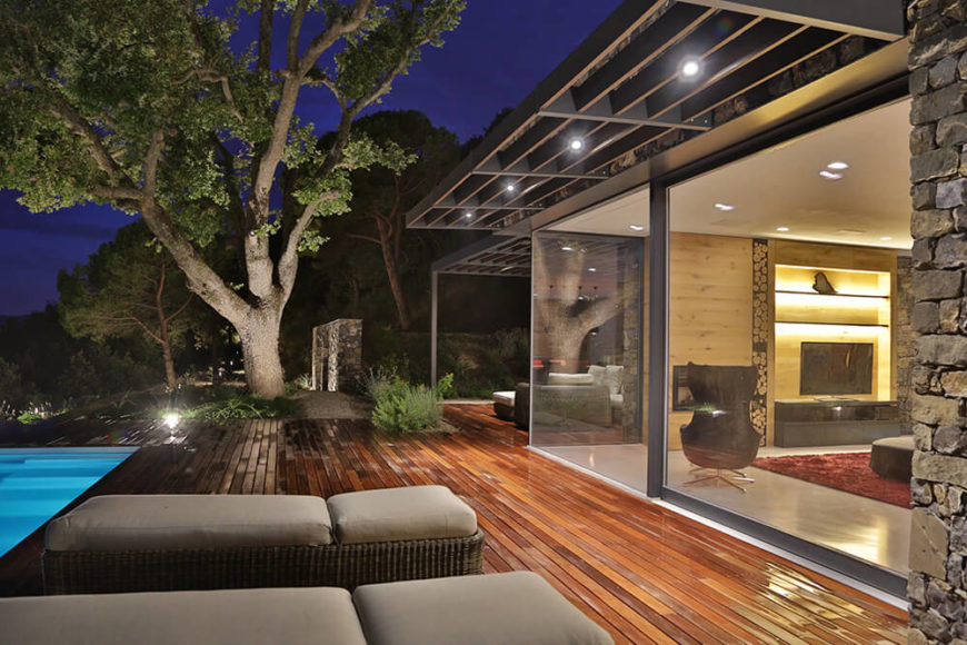 Sharp overhangs provide shade and night lighting for the deck, as they ease the transition from indoors to out. With the home sunk into the landscape, the trees and surrounding foliage appear to wrap it entirely.