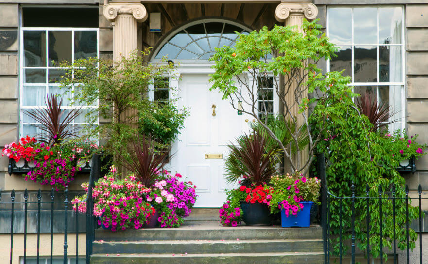 Flanking The Entryway Are Honeysuckles, Petunias, Red Sensation Cordylines  And Other Greenery Which Seem