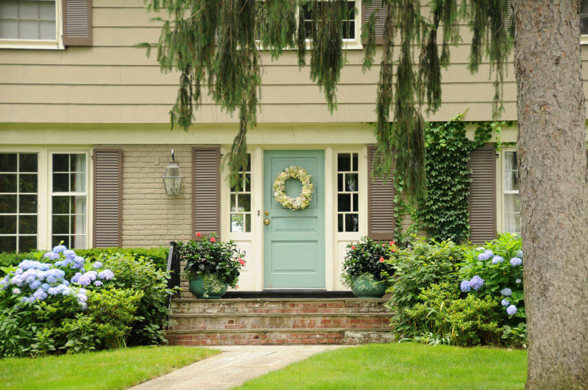 A white floral wreath hangs on the door while two green pots are in charge of the ornamental plants. There are also Ivy vines climbing on the walls while the rest of the greenery and mophead hydrangeas rest contented on a carpeting turf grass.