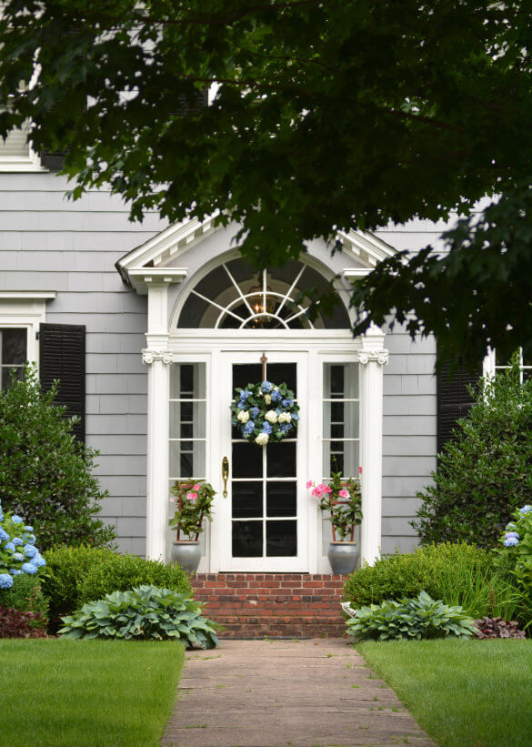 A wreath of mophead hydrangeas gives light to the front door while a pair of silver pots with flowering vines give amicable support to the decoration.