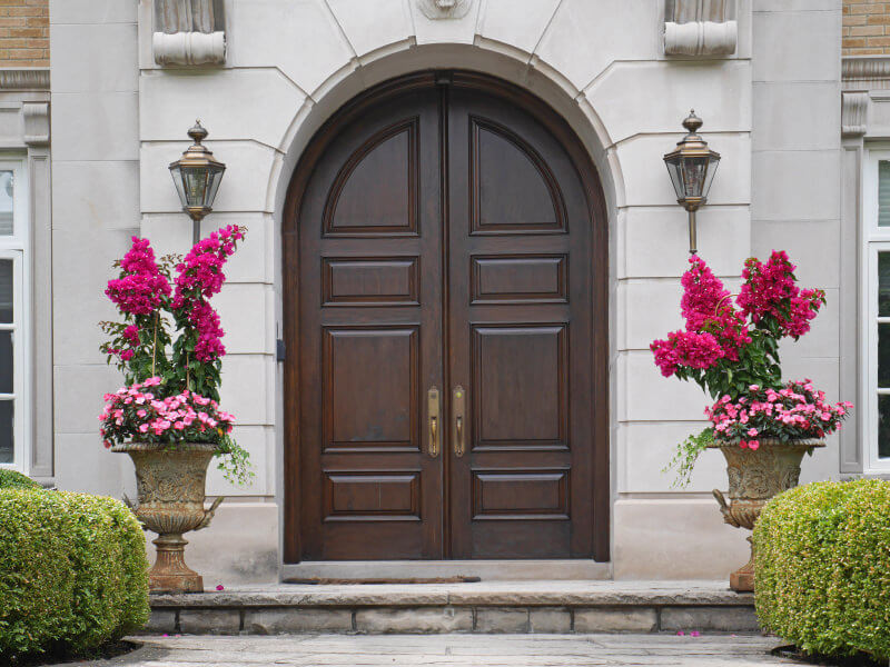 Twining bougainvillea with string vines and petunia blossoms planted in gothic pots highlight the entryway.