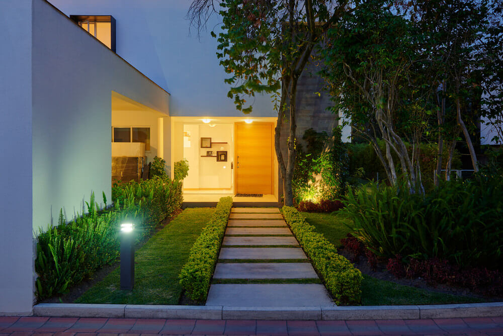 Even a dim light cannot conceal the beauty of nature. Here you can find ferns, grasses and trees that usher tranquility towards the front door.