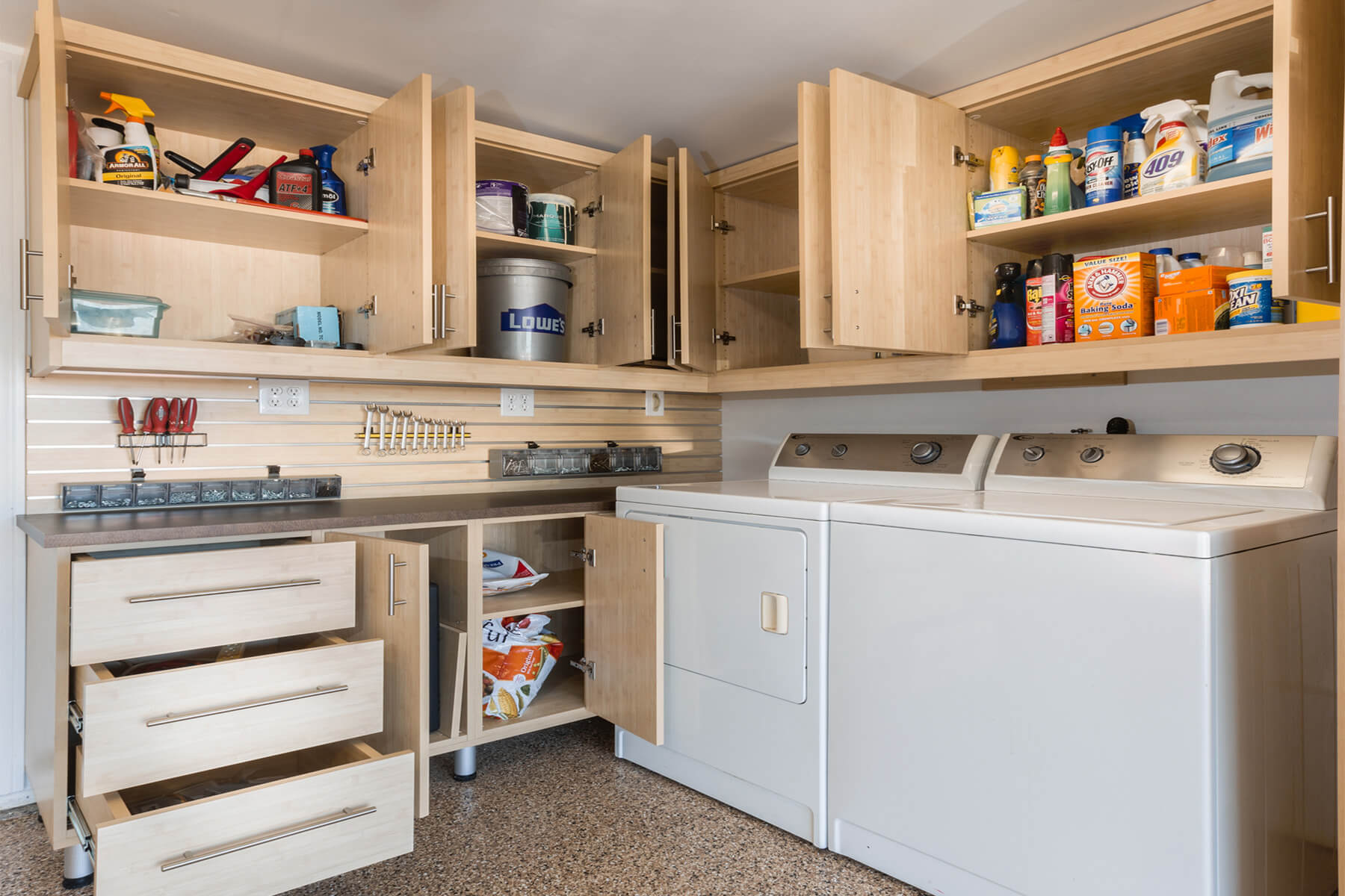 This very functional laundry room offers a wide choice of storage and cabinets from the ceiling wood cabinets down to the floor cabinets.