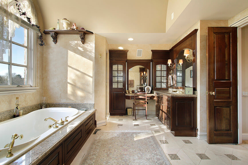 Authentic and classic bathroom highlighted with brown wood vanities, light brown floor tiling and patterns, and neutralized with cool light brown walls.