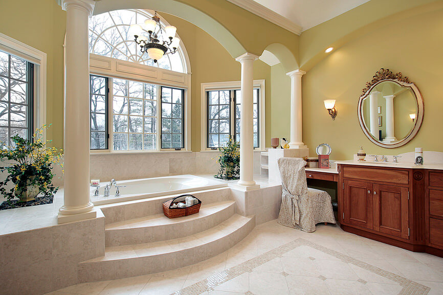 An old fashioned bathroom style colored with brown highlights. Light tan color on the flooring tiles and patterns, while the brown wood vanities sit against the greenish brown wall.