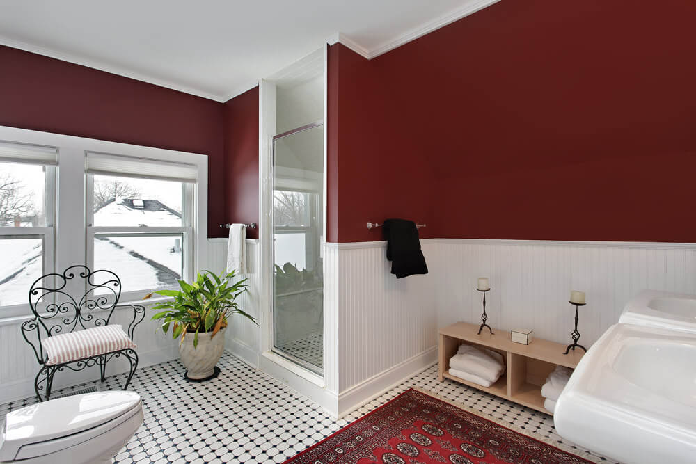 Patterned black and white floor texture with red floor carpet. The contrast of the red oxide and white colored wall adds a strong mood to the design. Moreover, the tan wood vanity and add on like the cushioned chair and marbled potted plants show off a cool atmosphere.