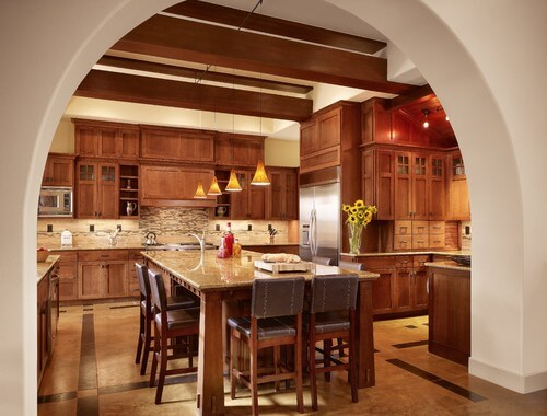 Seen through a wide archway, this kitchen features custom cabinetry, exposed wooden beams, and natural stone on both the floors and in the backsplash. The details are understated, but stunning.