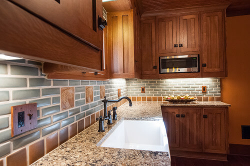 The backsplash of this kitchen is the main event, featuring soft colors and a few handcrafted tiles behind the sink. The details on the cabinetry are simple, but effective.