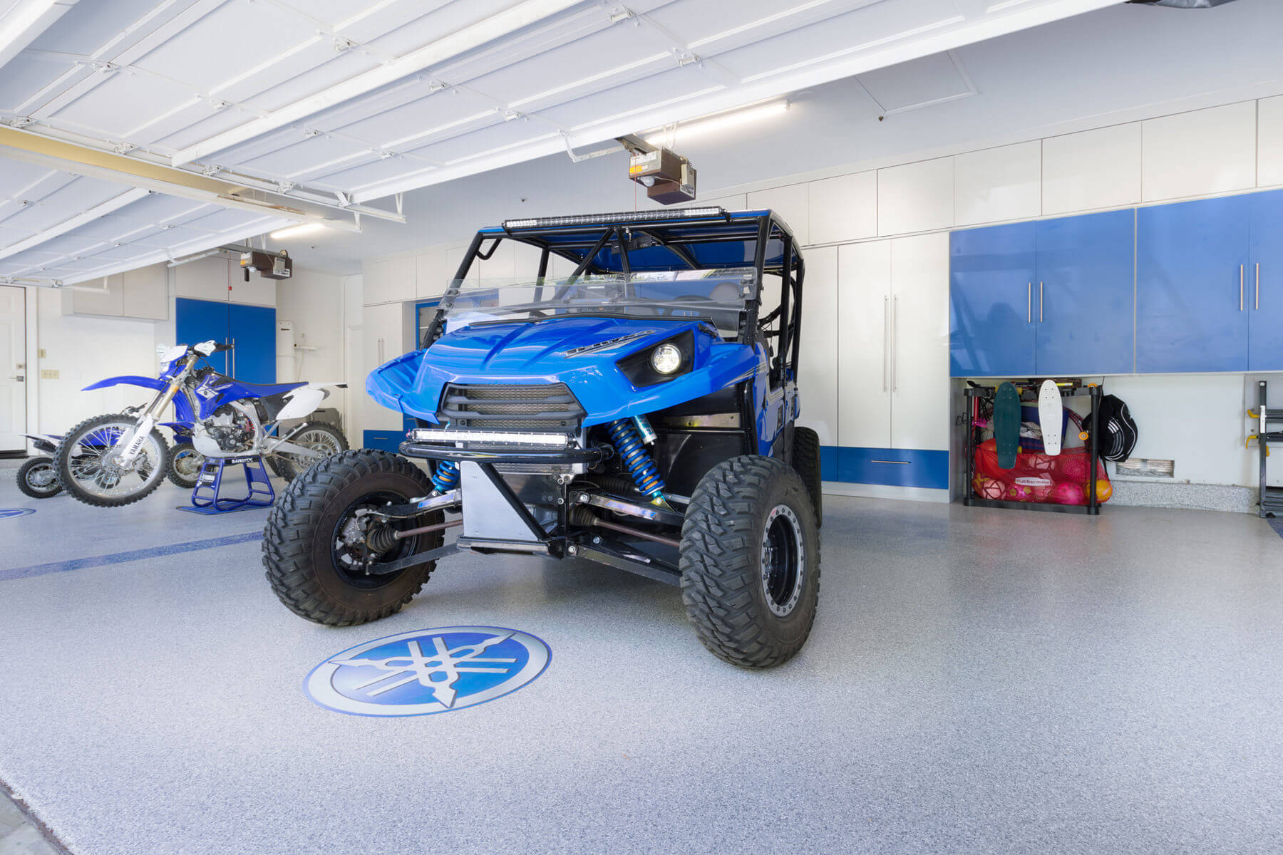This garage filled with blue and white high gloss melamine cabinets match colors with the blue-colored vehicles.