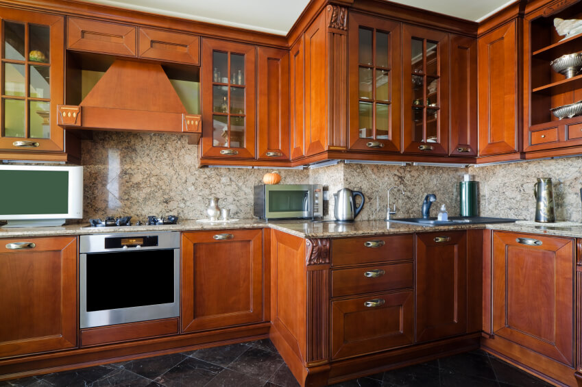 This kitchen focuses more on the rich stain than the grain of the wood, and features a few small ornate touches on the cabinets. The combination of traditional cabinets with glass-faced and open shelving is stunning.
