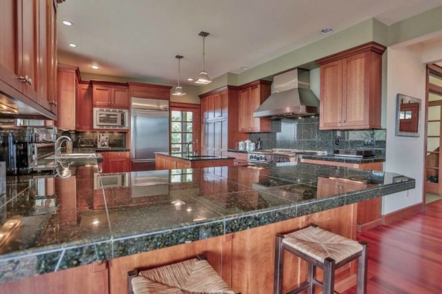 Granite tile countertops are unusual, since slab countertops are more popular overall, but they do fit the theme of a Craftsman kitchen. The simple, beautiful natural wood cabinetry is the most stunning feature of this kitchen design.